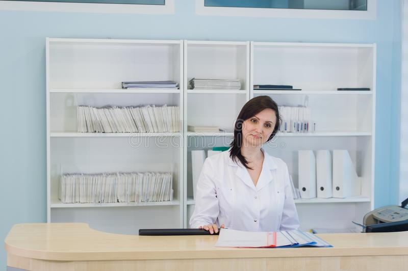 Young practitioner doctor working at the clinic reception desk, she is answering phone calls and scheduling appointments royalty free stock image