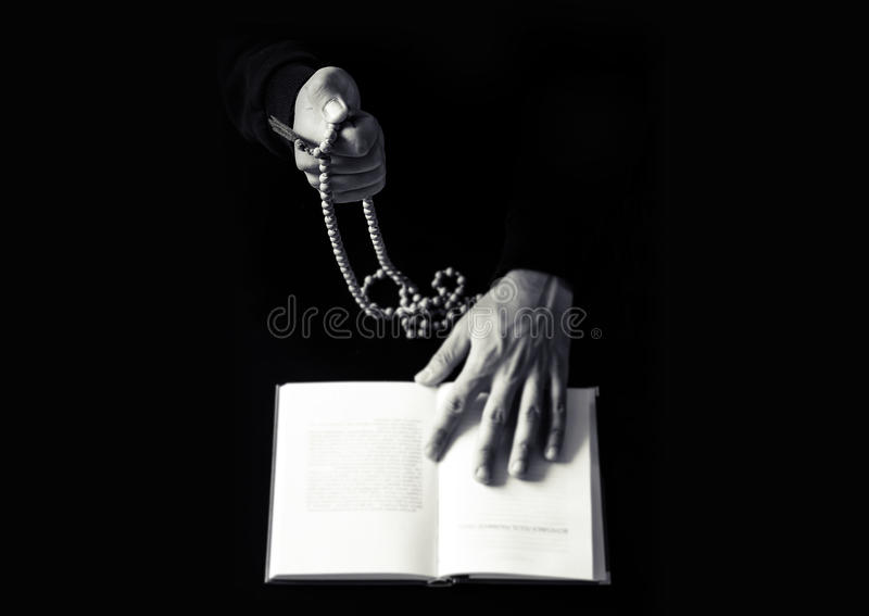 Young praying hands with wooden rosary and Holy Bible. stock photography