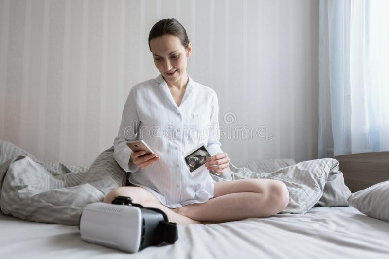 Young pregnant Caucasian woman sitting on bed with smartphone and ultrasound picture and vr glasses stock photos