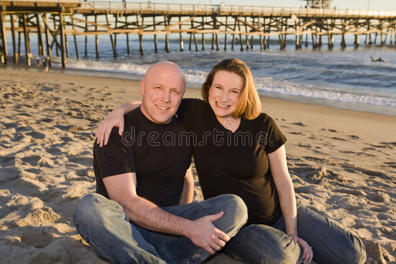 Young Pregnant Couple on the Beach. With Pier in Background at Sunset stock image