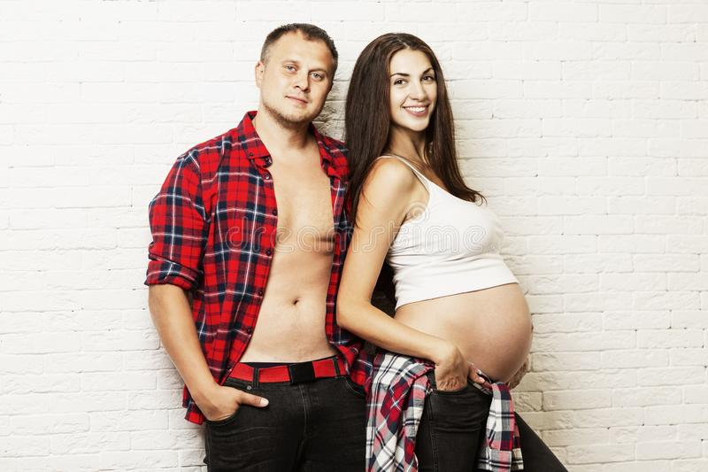 Young pregnant couple hugging and smiling. Waiting for birth and tender relationship royalty free stock images