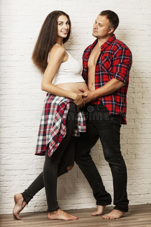 Young pregnant couple hugging and smiling. Waiting for birth and tender relationship. stock image