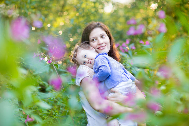Young pregnant mother holding her tired baby daughter stock image