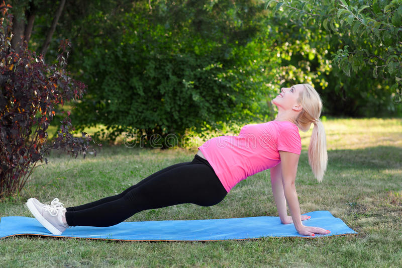 Young pregnant stretching outdoor, fitness stock photo