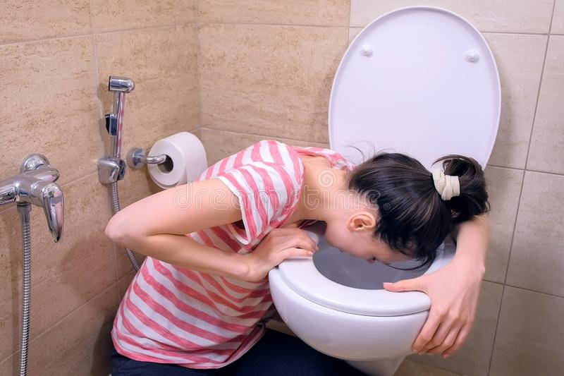 Young pregnant tired woman is vomiting in toilet sitting on the floor at home. Young pregnant tired woman is vomiting in toilet sitting on the floor at home stock images