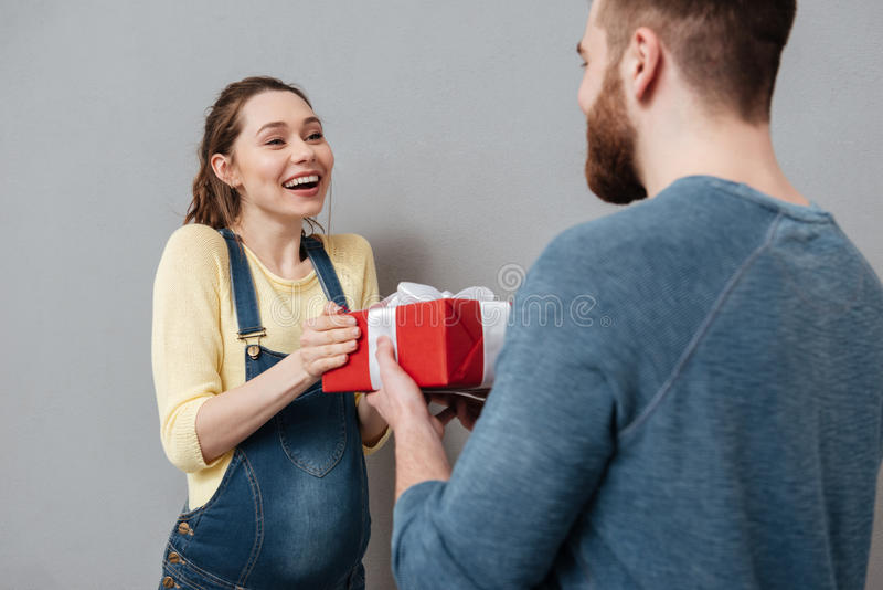Young pregnant woman accepting present from her husband. Cropped image of a young pregnant women accepting present from her husband over gray background royalty free stock photography