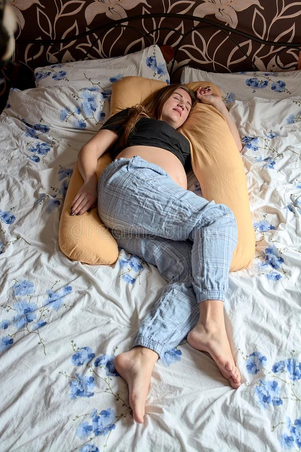 Young pregnant woman. Pregnant beautiful woman sleeps on maternity pillow in bed royalty free stock photo