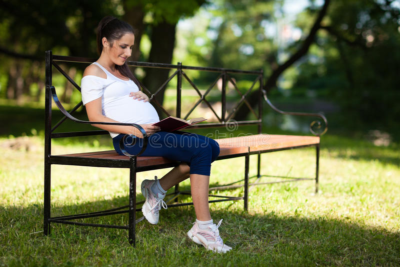 Young pregnant  woman with book sits in the park.