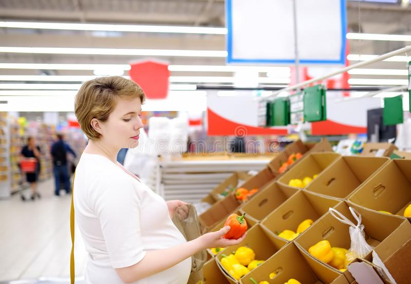 Young pregnant woman choosing fruits and vegetables in mesh shopping bag in supermarket stock photo