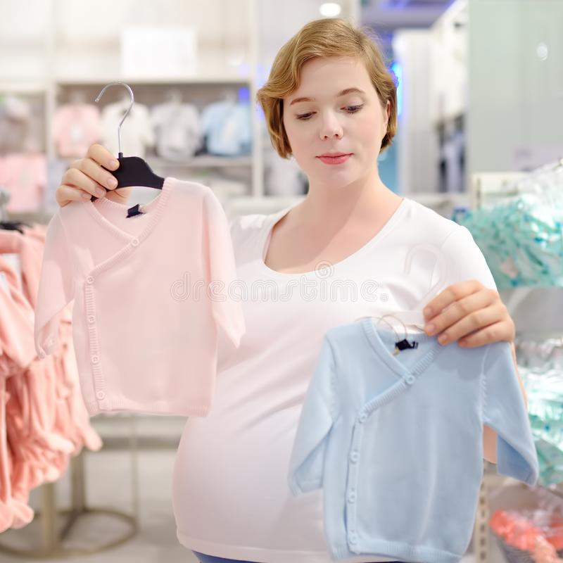 Young pregnant woman choosing pink or blue clothes in the store for newborns royalty free stock images