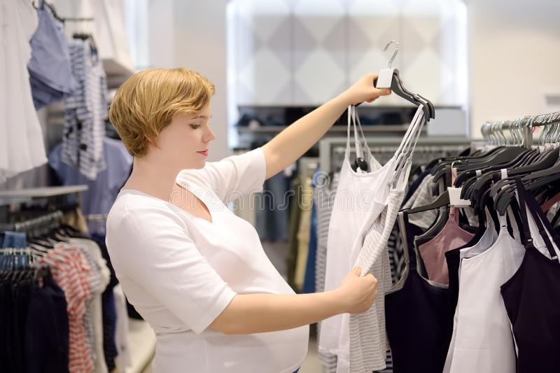 Young pregnant woman choosing underwear for breastfeeding in store stock images