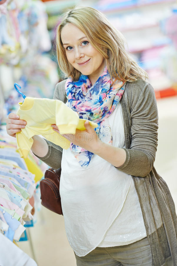Young pregnant woman at clothes shop stock photos