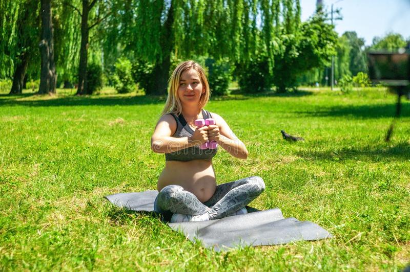 Young pregnant woman doing sport exercises on green grass in the park. stock photography