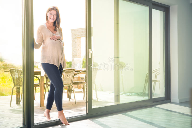Young pregnant woman entering house from garden royalty free stock image