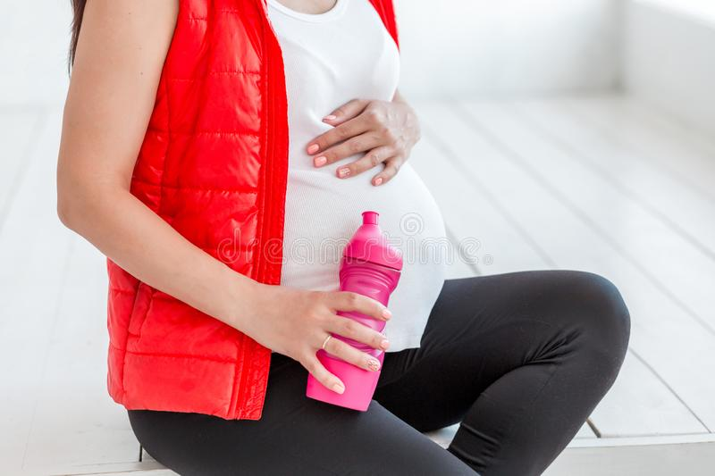 Young pregnant woman after fitness whith water bottle. Sport during pregnancy royalty free stock image