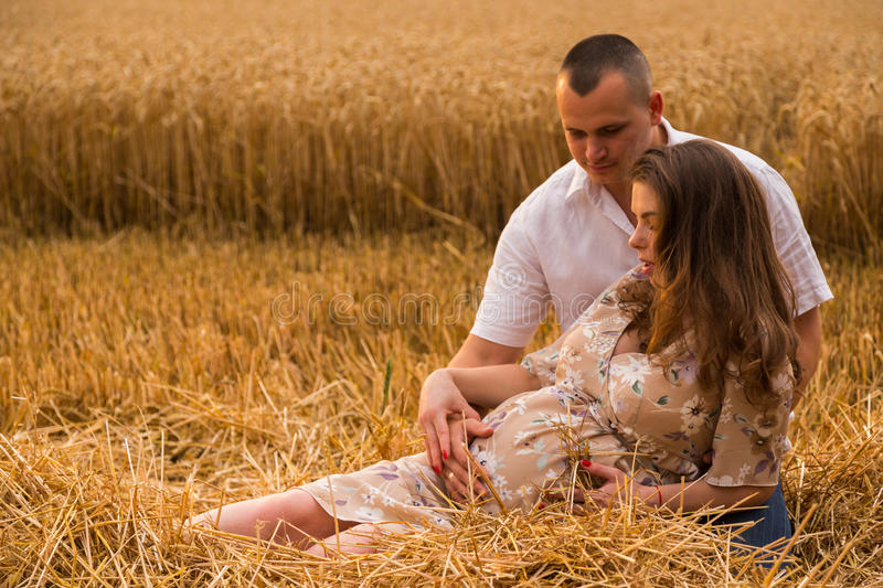 A young pregnant woman with her husband among the wheat field royalty free stock photography