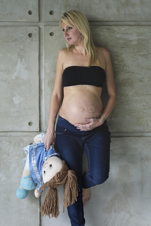 Young pregnant woman with her unborn child. And rag doll royalty free stock images
