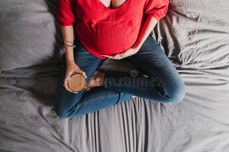 young pregnant woman at home holding a cup of decaffeinated coffee stock images