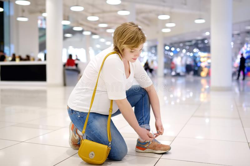 Young pregnant woman lacing up sneakers in hall of shopping mall. Problems of pregnant women with great abdomen lace up shoes stock photo