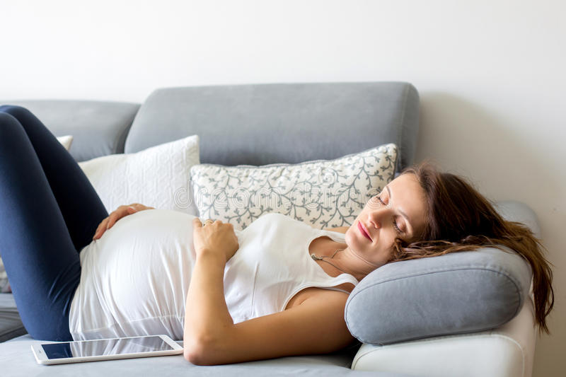 Young pregnant woman, lying down on couch in living room, relaxing stock images