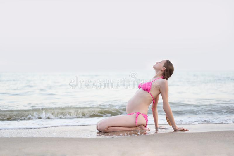 Young pregnant woman is practicing yoga sitting on the sea beach. Summer day royalty free stock photos