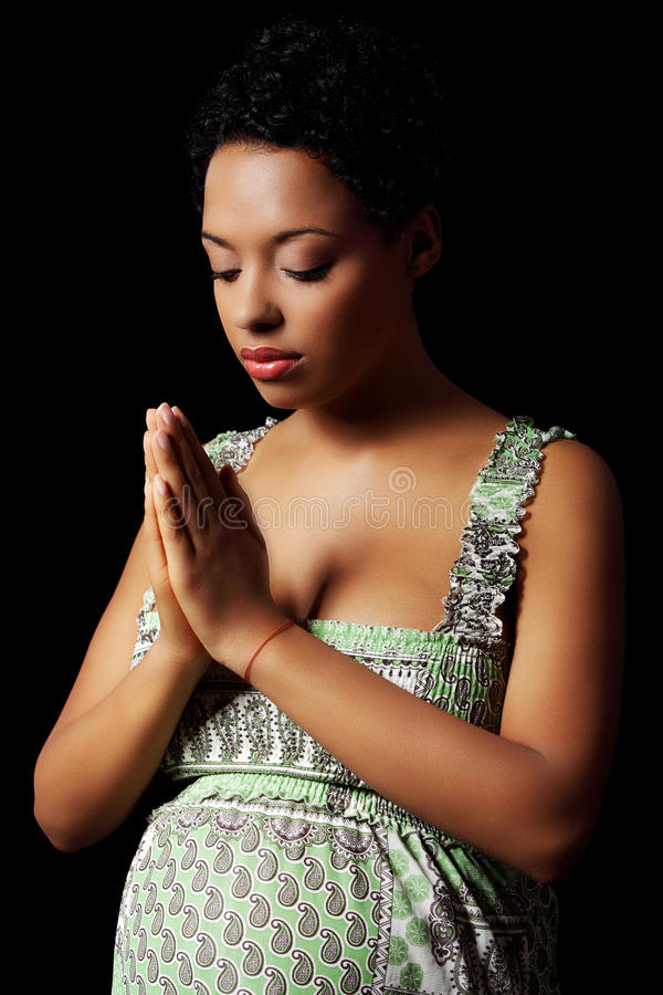 Young pregnant woman praying royalty free stock photography