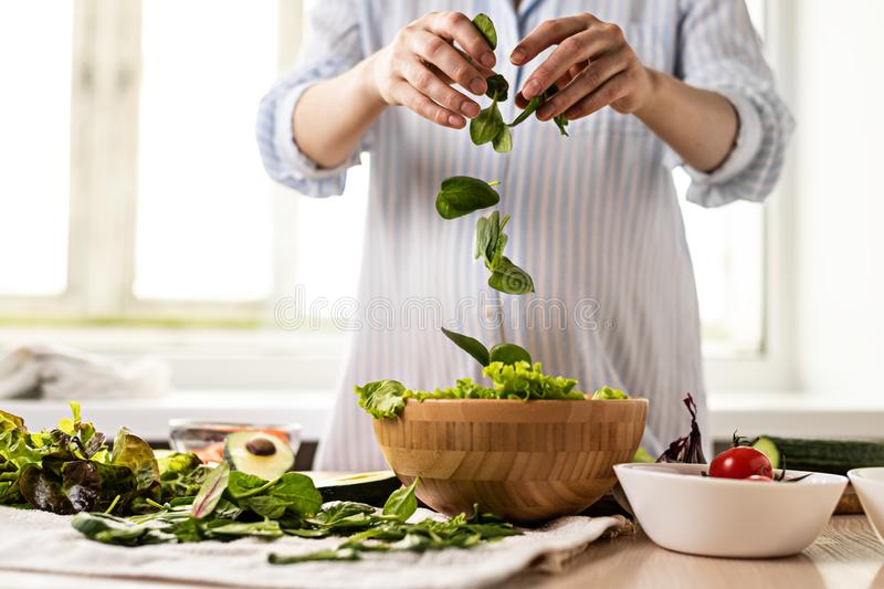 Young pregnant woman prepares healthy salad of greens and vegetables stock photos