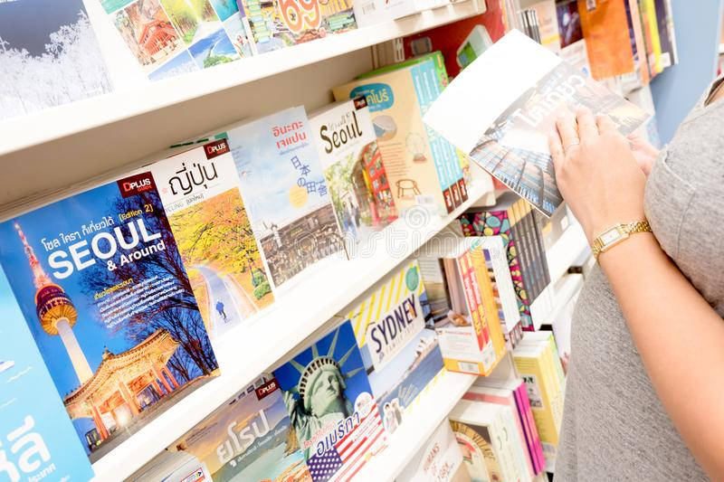 Young pregnant woman reading Tokyo travel guide book in bookstore. stock photography