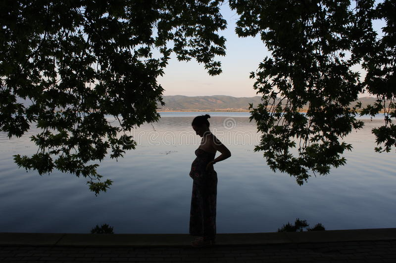 Young and pregnant woman relaxing next to the lake stock image