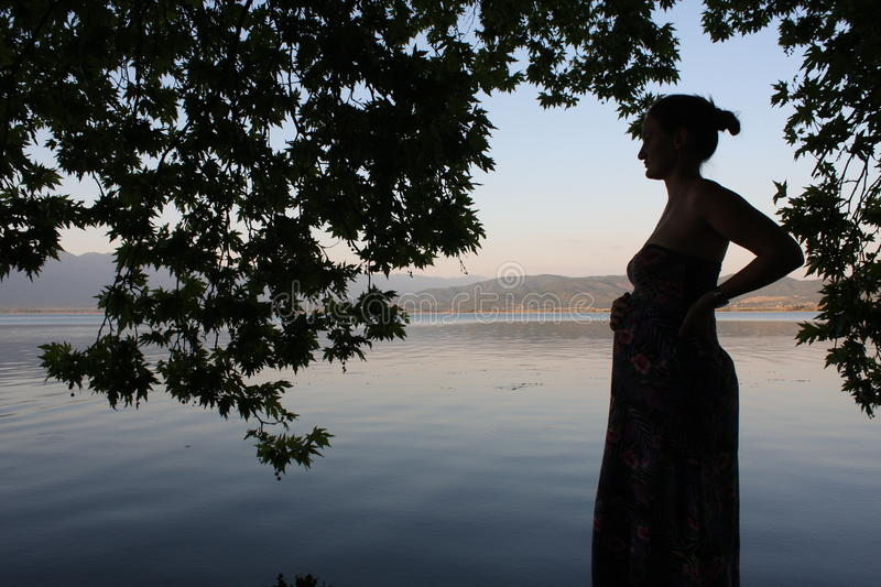 Young and pregnant woman relaxing next to the lake stock images
