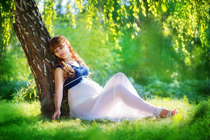 Young pregnant woman relaxing in park outdoors, healthy pregnancy. Happy pregnant woman on nature. Beautiful pregnant woman royalty free stock images