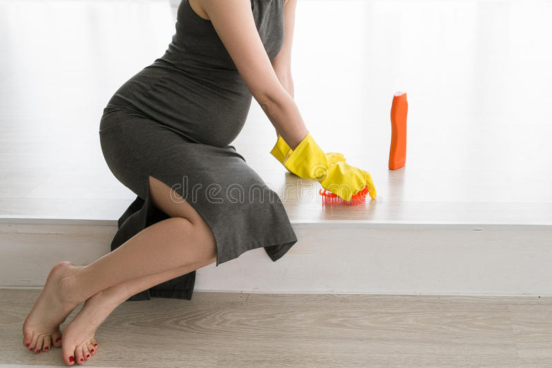 Young pregnant woman is scrubbing floor stock images