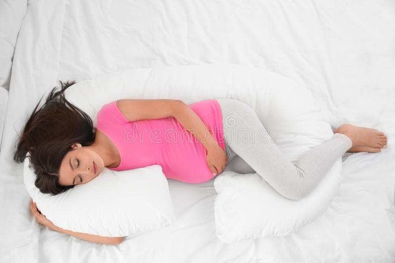 Young pregnant woman sleeping on maternity pillow royalty free stock photos