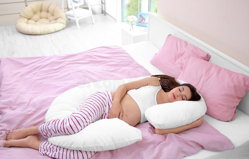 Young pregnant woman sleeping on maternity pillow stock photos