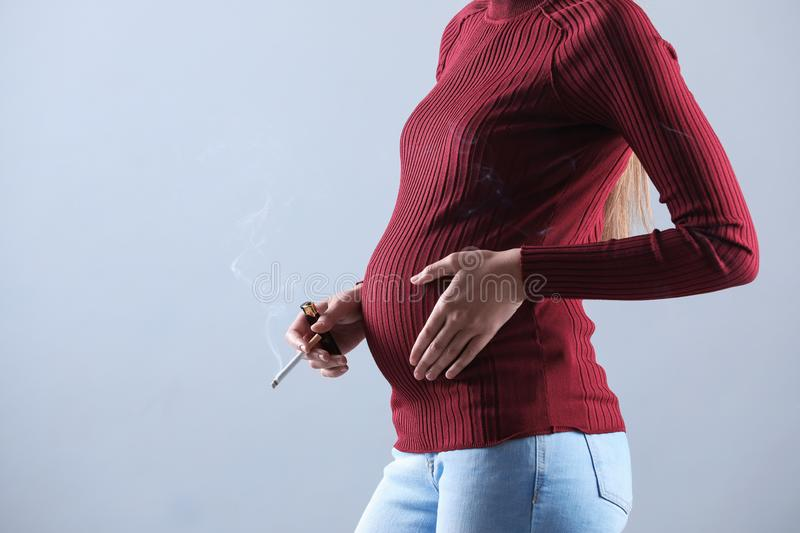 Young pregnant woman smoking cigarette on grey, closeup. Space for text. Young pregnant woman smoking cigarette on grey background, closeup. Space for text stock photos