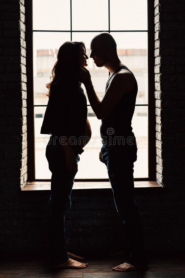 A young pregnant woman is standing with her husband near the window in the studio royalty free stock photo
