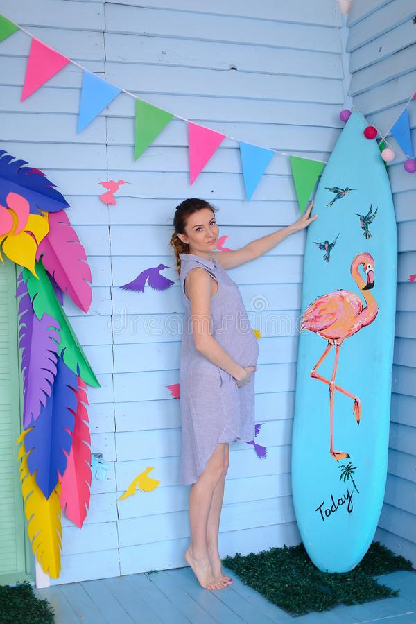 Young pregnant woman standing near surfboard and decorated children house. royalty free stock images