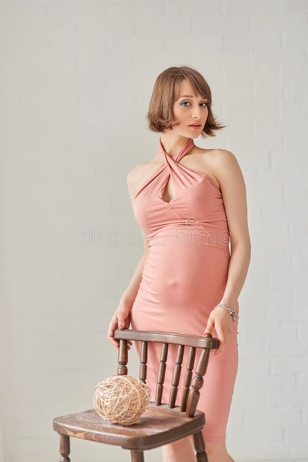 Young pregnant woman in a stylish pink dress standing in a bright room holding hands on the back of a chair stock image