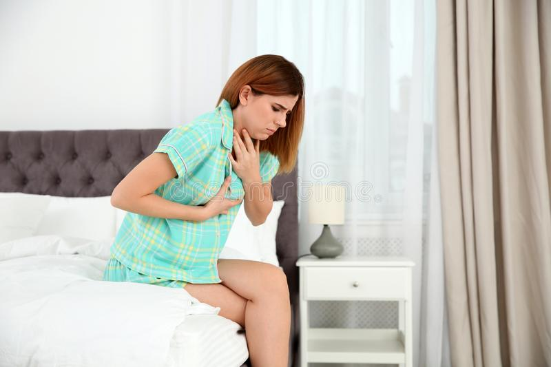 Young pregnant woman suffering from morning sickness at home. Space for text royalty free stock photo