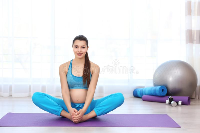 Young pregnant woman training in gym. royalty free stock image