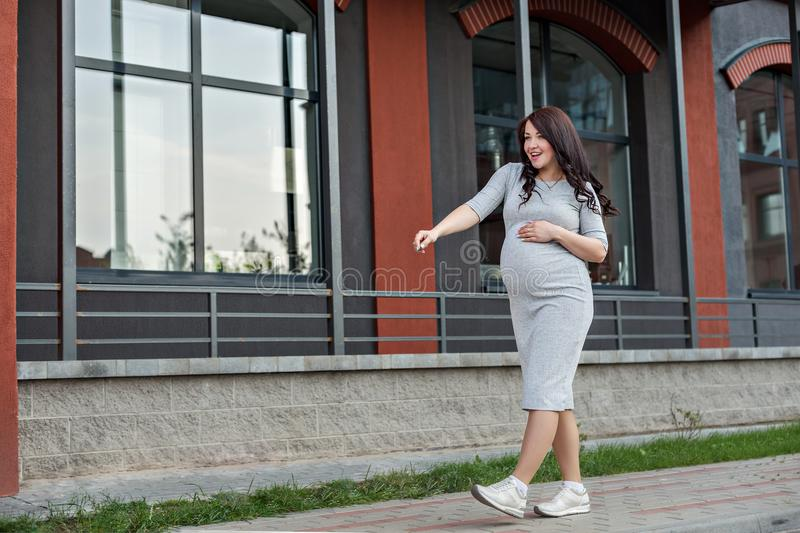 A young pregnant woman walking dancing along the city windows royalty free stock image