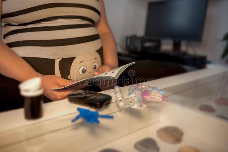 A young pregnant woman wants to measure her blood sugar. stock images