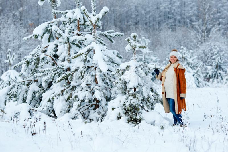 Young pregnant woman wearing warm clothes having fun on winter forest royalty free stock images
