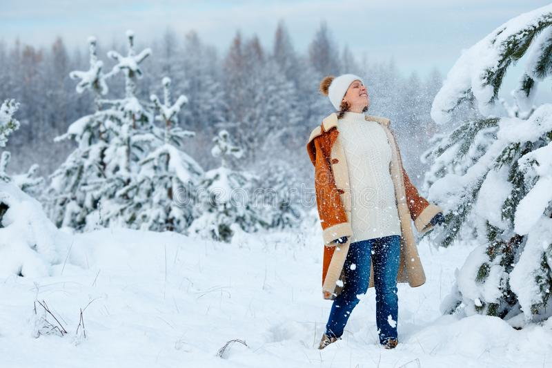 Young pregnant woman wearing warm clothes having fun on winter forest stock photos