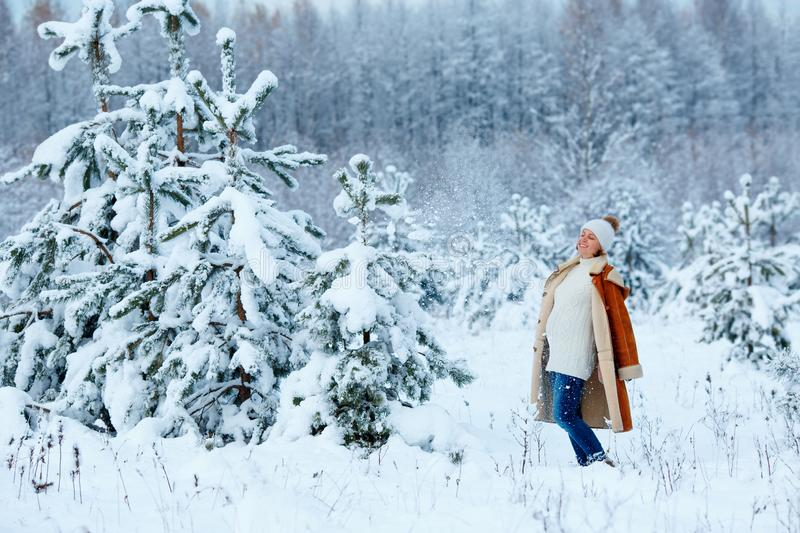 Young pregnant woman wearing warm clothes having fun on winter forest stock image