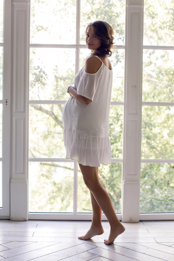 Young pregnant woman in white dress in the studio royalty free stock images