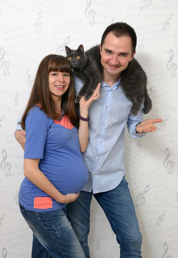 Young pregnant woman and young man with a cat stock images