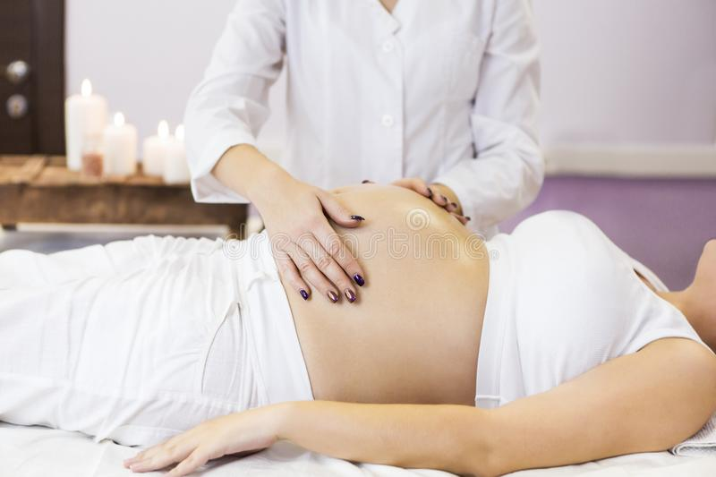 Pregnant woman have massage treatment at spa salon. Young pregnant women have massage treatment at spa salon royalty free stock photos