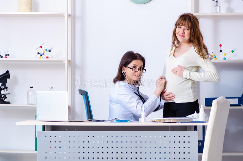 Young pregnant woman visiting experienced doctor gynecologist. The young pregnant women visiting experienced doctor gynecologist royalty free stock image