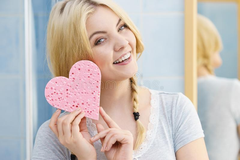 Blonde woman in braids holding heart. Young pretty adorable woman having two cute braids on blonde hair holding pink sponge in heart shape. Haircare and stock images
